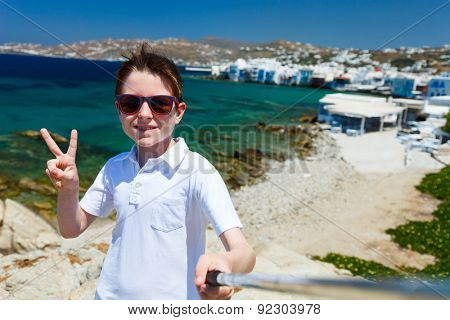 Cute teenage tourist making selfie with a stick at place overlooking Little Venice area on Mykonos island, Greece