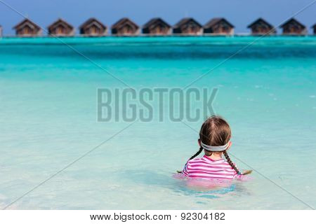 Little girl in a colorful sun protection swimwear on vacation swimming in a shallow water at tropical lagoon