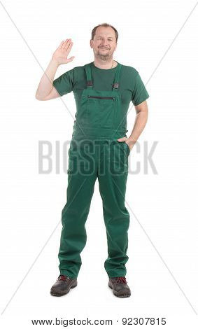 Worker in green overalls with ok sign.
