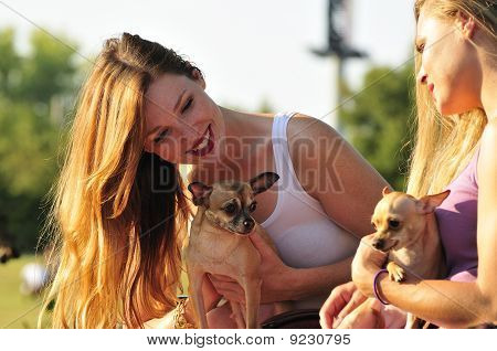 Two Women Playing With Cute Puppies