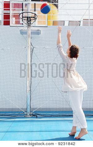 Brunette Woman In White Dress Throws Ball In Basket