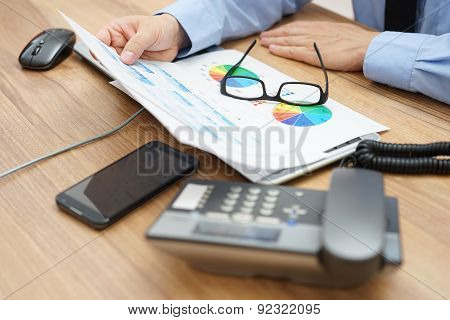 Busy Businessman Analyzing A Lot Of  Graphs And Business Data At  The Desk