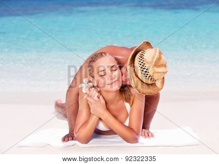 Loving couple on the beach, lying down on sandy coast and kissing, enjoying honeymoon vacation, summer vacation concept