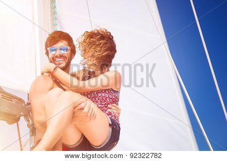 Joyful couple on sailboat, handsome man carrying on hands his lovely girlfriend, spending honeymoon vacation in the sea, active summer time vacation