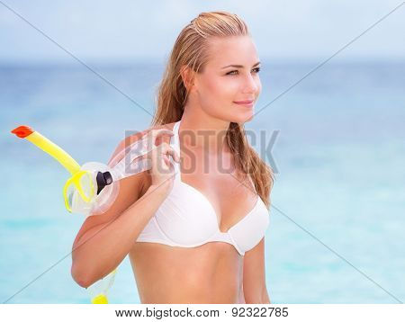 Portrait of happy beautiful girl standing on seashore with a diving mask in hand, having fun on the beach, enjoying summer activities