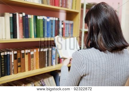 Back view woman in a library with book at self-education