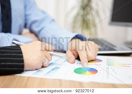 Businessman And Businesswoman Discussing About Company Report In Office