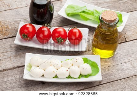 Tomatoes, mozzarella and green salad leaves with condiments on wooden table background
