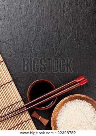 Japanese sushi chopsticks over soy sauce bowl and rice on black stone background. Top view with copy space