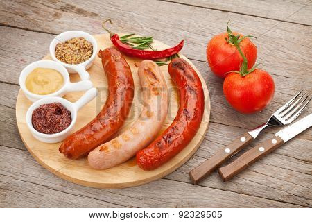 Various grilled sausages with condiments and tomatoes on cutting board