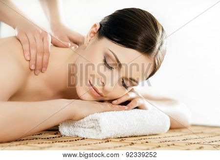 Young and healthy woman in spa salon. Traditional Swedish massage therapy and beauty treatments.