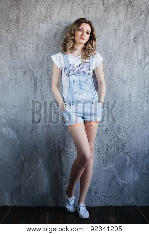 beautiful girl with curly hair in denim overalls