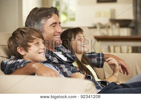 Father And Two Children Sitting On Sofa At Home Watching TV Together