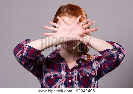 Woman With Her Hands Signaling To Stop Isolated On A Grey Background
