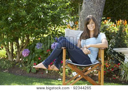 Teenage Girl Sitting Outdoors In Garden Chair
