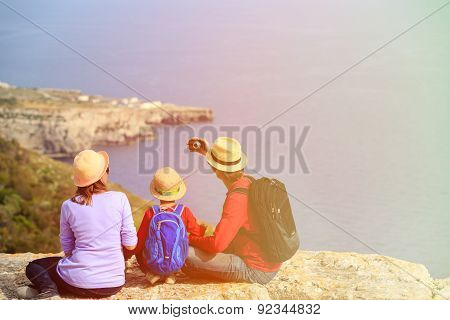 family with small kid making selfie while travel