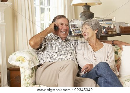 Retired Senior Couple Sitting On Sofa Talking On Phone At Home Together