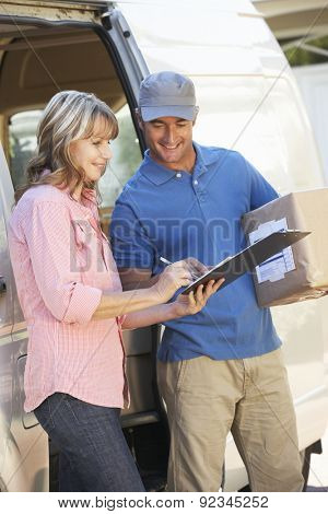Woman Signing For Packager Delivered By Courier