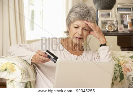 Frustrated Retired Senior Woman Sitting On Sofa At Home Using Laptop