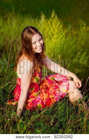 Red-haired Young Woman With Long Ginger Hair And Closed Eyes Sitting On Grass And Smiling
