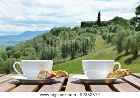Two coffee cups and cantuccini on the wooden table against olive grove. Tuscany, Italy