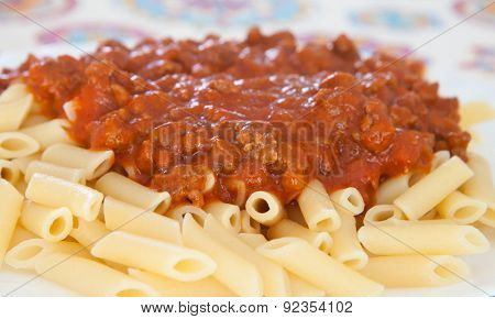 Delicious plate of macaroni with tomato close up