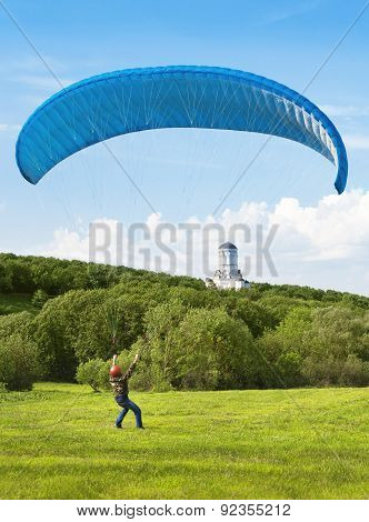 Paraglider. Man With Parachute Struggling With The Wind. In The Background Can Be Seen The Orthodox