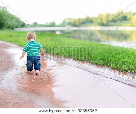 Child Walks On The Puddles After The Rain