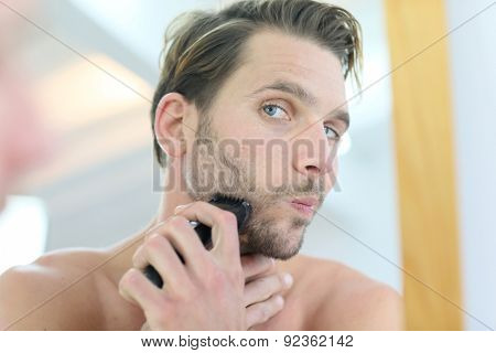 Man in front of mirror using electronic shaver