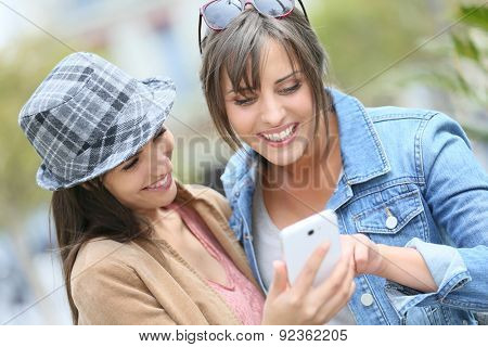 Girlfriends using smarphone in town