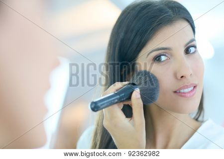 Brunette woman using powder brush in front of mirror