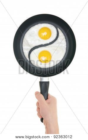 Fried Eggs In The Form Of Yin And Yang On Pan. Pan In Hand On White Background