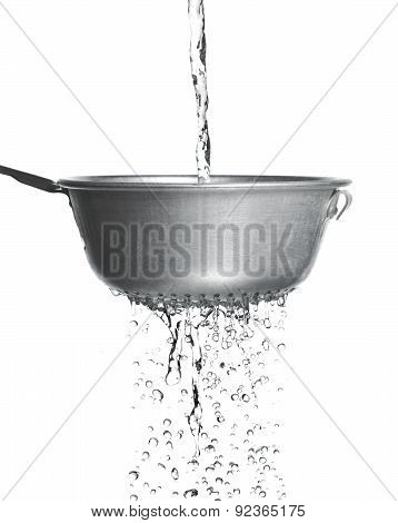 Water poured through a strainer on a white background
