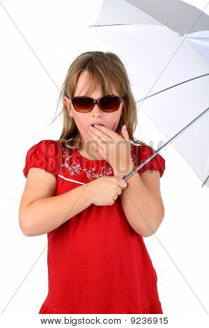 Small girl in red clothes under umbrella with sunglasses looking shocked at camera isolated on white