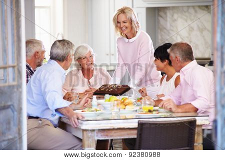 Woman Serving Cake To Group Of Friends Enjoying Meal At Home