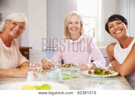 Portrait Of Mature Female Friends Enjoying Meal At Home