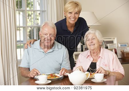 Senior Couple Enjoying Meal Together At Home With Home Help