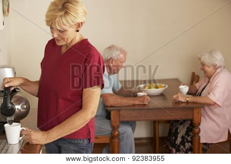 Home Help Sharing Cup Of Tea With Senior Couple In Kitchen