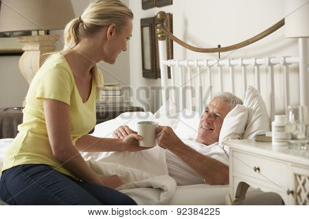 Adult Daughter Giving Senior Male Parent Hot Drink In Bed At Home
