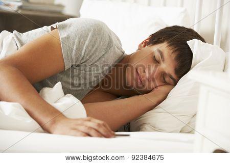 Teenage Boy Asleep In Bed At Home