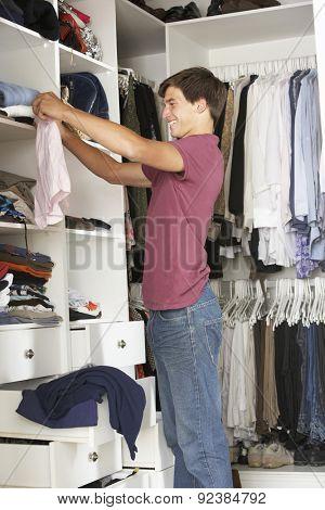 Teenage Boy Choosing Clothes From Wardrobe In Bedroom