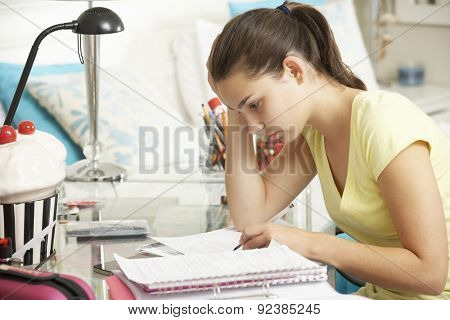 Teenage Girl Studying At Desk In Bedroom
