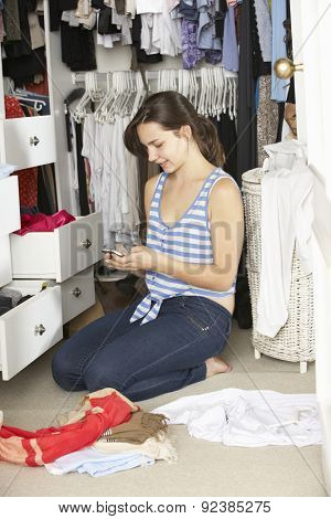 Teenage Girl On Mobile Phone Surrounded By Clothes In Wardrobe