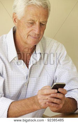 Senior Man Sending Text Message Sitting On Sofa