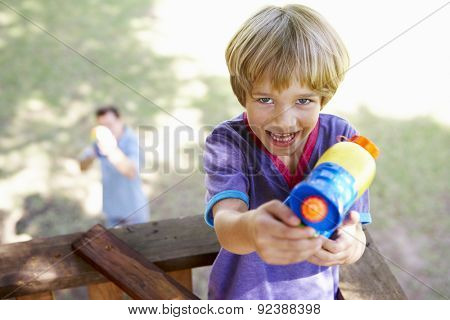 Father And Son Having Water Pistol Fight In Tree House