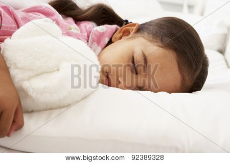 Young Girl Asleep In Bed With Cuddly Toy