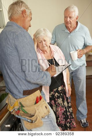Repairman Giving Senior Couple Estimate For Repair