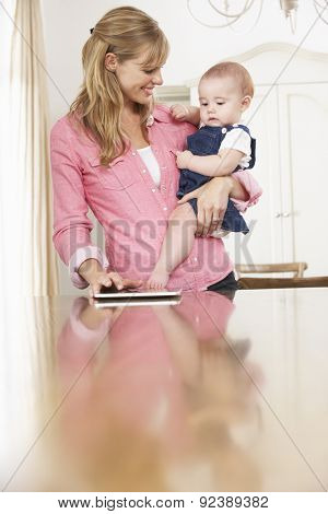 Mother Holding Baby Daughter Whilst Using Digital Tablet