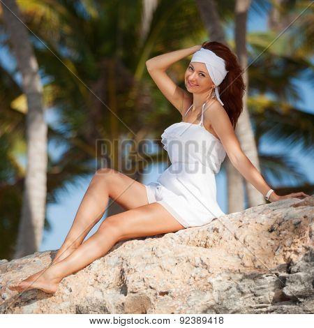 Fashion woman relaxing under palm trees