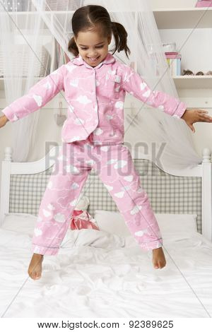 Young Girl Wearing Pajamas Jumping On Bed